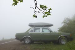 Old vintage car with roof rack in a mist on the road. S stock image