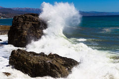 Crimea. Alushta. Sea. The wave beats against the rock and spread. S out with splashes. Bright blue sky and mountains royalty free stock photo