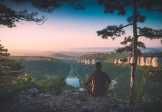 Crimea mountain valley in a light of sunrise. Instagram stylization. Hiker sitting on a cliff edge and enjoy Crimea mountain valley in a light of sunrise. View royalty free stock photo