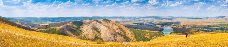 Crimea pano. Panorama of Crimea mountain valley with woman-hiker and kid, who enjoy landscape Stock Photo