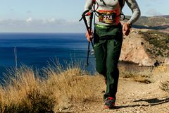 Male athlete runner with trekking poles runnning marine trail royalty free stock photos