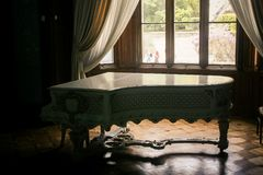Crimea Vorontsov Palace Interior Grand Piano by Lit Window. Closeup Vorontsov palace interior room with white grand piano near lit window with curtains Crimea royalty free stock images