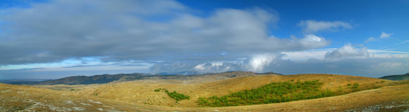 Crimean mountains plateau with cloudscape. Crimean mountains plateau with clouds at horizon and hills Stock Photos