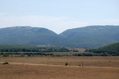 Crimean mountains. The ridge of the Crimean mountains and the valley at sunny summer midday Royalty Free Stock Image