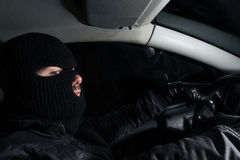 Criminal. Masked man sitting in a car Royalty Free Stock Image