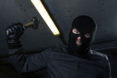 Criminal. Masked criminal with a hammer Stock Photography