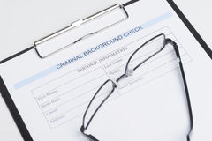 Criminal background check document. Close-up of criminal background check document with a eyeglasses lying on it royalty free stock photo