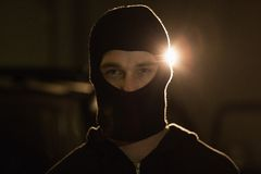 Criminal in balaclava looking at camera Royalty Free Stock Image