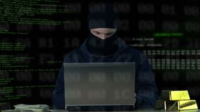 Criminal in balaclava working on laptop, hacking bank security system, data code. Stock footage stock video footage