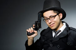 The criminal in black coat holding hadgun against Stock Image