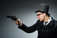 The criminal in black coat holding hadgun against Royalty Free Stock Photo
