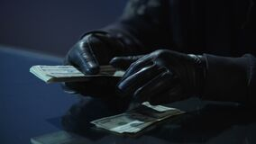 Criminal in black gloves counting bundle of money earned for committing crime
