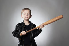 Criminal boy with baseball bat.Funny child in leather coat. Little thug Stock Photo