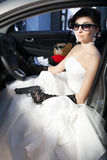 Criminal bride. With a gun and money driving with selective focus Stock Images