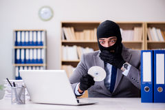 The criminal businessman with balaclava in office. Criminal businessman with balaclava in office Royalty Free Stock Images