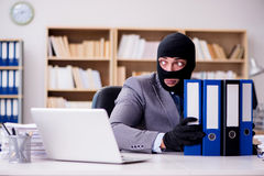 The criminal businessman with balaclava in office. Criminal businessman with balaclava in office Royalty Free Stock Photography