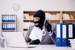 The criminal businessman with balaclava in office. Criminal businessman with balaclava in office Stock Photo