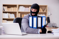 The criminal businessman with balaclava in office Stock Photos