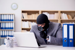 The criminal businessman with balaclava in office Stock Photo