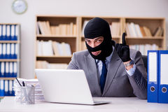 The criminal businessman with balaclava in office. Criminal businessman with balaclava in office Stock Photography