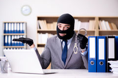 The criminal businessman wearing balaclava in office Royalty Free Stock Photos