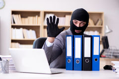 The criminal businessman wearing balaclava in office. Criminal businessman wearing balaclava in office Stock Photo