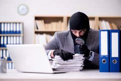 The criminal businessman wearing balaclava in office. Criminal businessman wearing balaclava in office Stock Photography