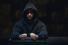 Criminal and computer. Young caught masked criminal hacking in computer royalty free stock image