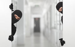 Criminal concept - robber hiding behind a empty white sign Stock Image
