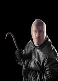 Criminal with crowbar. A criminal wearing pantyhose over his head to hide his identity carries a crowbar to commit a crime Royalty Free Stock Image