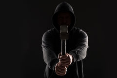 Criminal in dark clothes and balaclava with hammer stock image