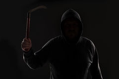 Criminal in dark clothes and balaclava with scythe Stock Photo