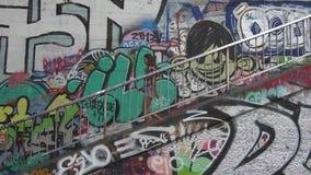 Criminal district. Woman walks near graffiti wall stock footage