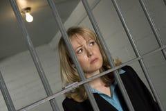 Criminal femenino detrás de barras en cárcel imagen de archivo