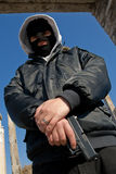 Criminal with a gun. Criminal man in hooded coat and black balaclava mask Royalty Free Stock Photos