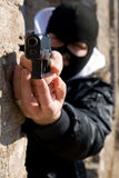 Criminal with a gun. Criminal in black mask aiming target, focus on pistol Royalty Free Stock Photography