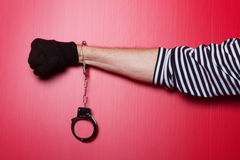 Criminal hand locked in handcuffs. Criminal hands locked in handcuffs on red backgound Stock Images
