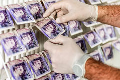 Criminal Hands In Gloves On British Sterling Pounds Notes On Clothes Dryer. Money Laundering Concept Royalty Free Stock Photography