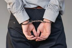 Criminal hands locked in handcuffs. Close-up view stock photos