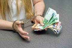 Criminal hands locked in handcuffs. Close-up view. Businesswoman in office in handcuffs holding a bribe of euro banknote. Close-up woman hands in handcuffs royalty free stock photo