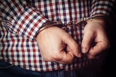 Criminal hands locked in handcuffs Stock Photo