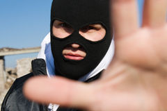 Criminal holding his hand in stop gesture. Criminal in black balaclava mask holding his hand in stop gesture Stock Image