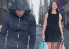 Criminal in hood in front of city street and Walking woman with shopping bags Stock Image