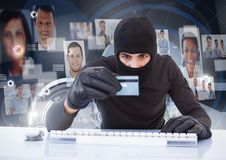 Criminal in hood on laptop with card in front of peoples profile faces Royalty Free Stock Images
