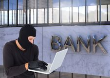 Criminal in hood on laptop in front of bank stock photos