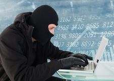 Criminal in hood on laptop in front of numbers interface royalty free stock photos