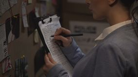 Criminal investigator drawing up record, writing down case details, inquiry. Stock footage stock video