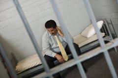 Criminal In Jail. Criminal men sitting on bed behind prison bars Royalty Free Stock Images