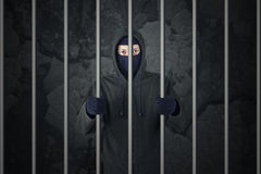 Criminal in jail. Behind bars. Arrested burglar in prison. Criminal with balaclava caught and arrested Royalty Free Stock Images