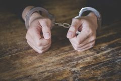 Criminal joven en esposas, cierre para arriba de las manos - imagen imágenes de archivo libres de regalías